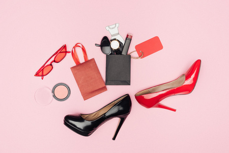 flat lay with high heels and little shopping bags with cosmetics and accessories isolated on pink Banque d'images - 110700638