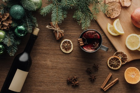 top view of cup of mulled wine and fruits on wooden tabletop, christmas concept