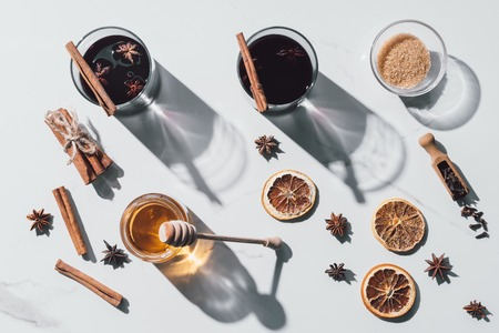 top view of glasses of mulled wine, honey and brown sugar on white tabletop