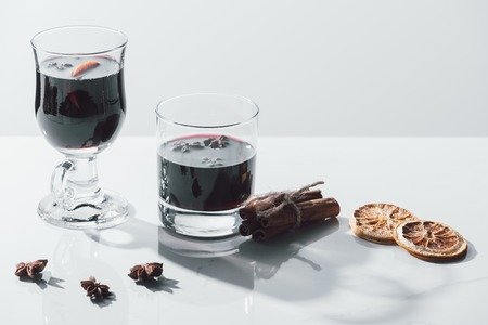 mulled wine in glasses and cinnamon sticks on white tabletop