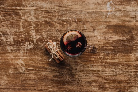 top view of cup of mulled wine and cinnamon sticks on wooden table