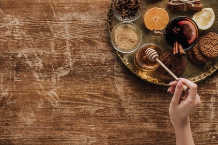 cropped image of woman holding honey stick at wooden table Фото со стока
