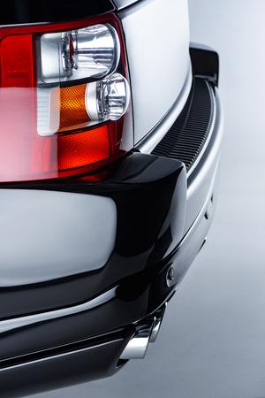 Close up view of rear headlight of luxury black car on grey backdrop Reklamní fotografie