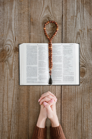 cropped shot of woman praying with holy bible and beads on wooden table
