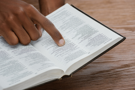 cropped shot of african american man reading holy bible and pointing at psalm Stockfoto