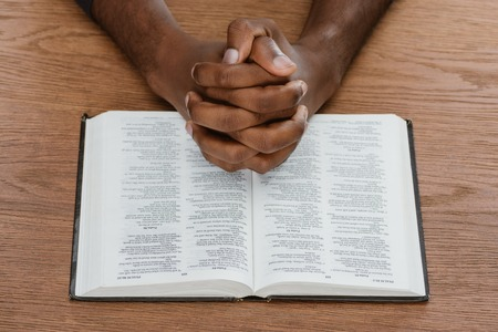 cropped shot of african american man praying with holy bible on wooden surface