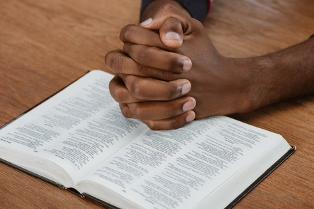 cropped shot of african american man praying with holy bible on wooden table 스톡 콘텐츠