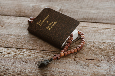 close-up shot of new testament book with beads on wooden surface Stock Photo