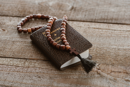 close-up shot of new testament book with beads on wooden table