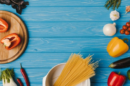 elevated view of uncooked pasta and vegetables on blue table Stock Photo