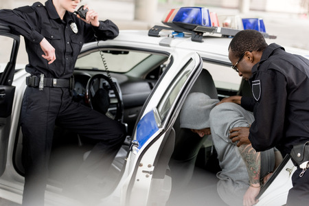 cropped shot of policewoman talking on radio set while her partner placing arrested man in car Reklamní fotografie - 110739491