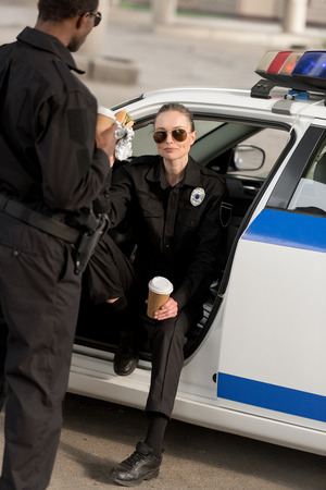 policewoman in sunglasses having lunch with african american partner