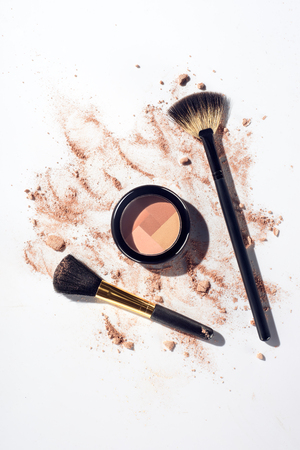 Pressed contouring powder with brushes on white background with scattered foundation