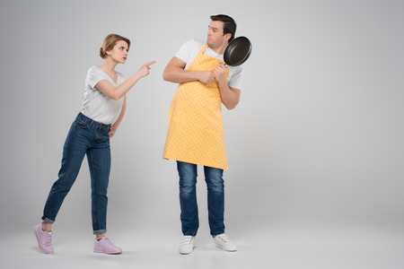 angry wife and frightened husband in apron with frying pan, feminism concept, isolated on grey Stock Photo