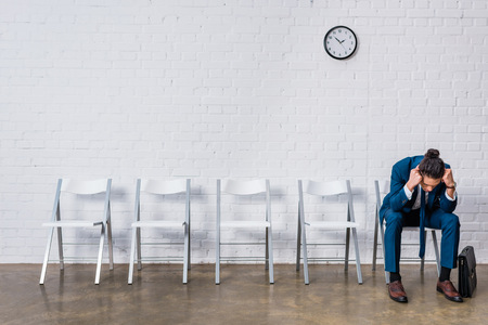 Stressed businessman sitting on chair and waiting for interview