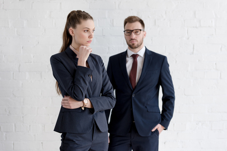 confident businessman and pensive businesswoman posing near white wall Stock Photo