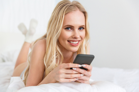 beautiful young blonde woman holding smartphone and smiling at camera while lying on bed