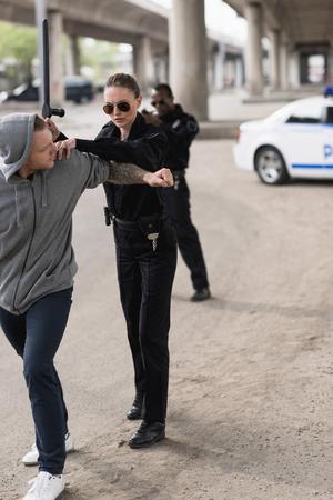 policière avec matraque arrêtant un bandit et un policier debout derrière et visant avec une arme de poing