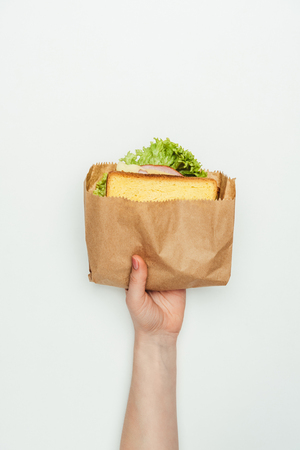 cropped image of woman holding sandwich in paper bag isolated on white