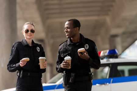 smiling police officers having coffee break with doughnuts Stockfoto