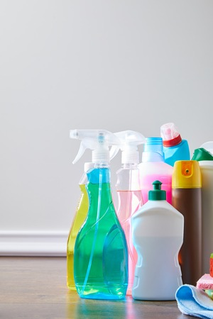 colored domestic supplies for spring cleaning on wooden floor Stock Photo