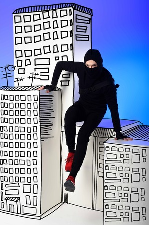 ninja in black clothing with katana behind getting across on drawing buildings on blue