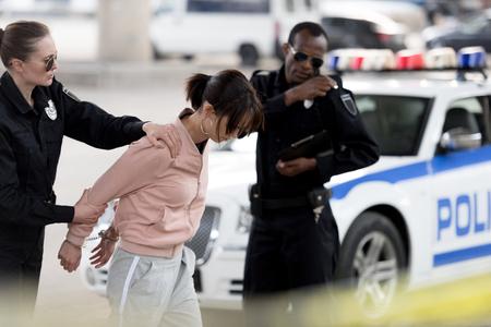 poliziotta che tiene arrestata una giovane donna mentre il suo partner parla alla radio portatile