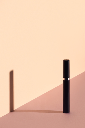 Single mascara tube on beige background