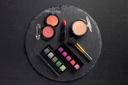Make up set with eye shadows and lipstick on round slate background Stock Photo