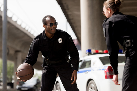 young police officers playing basketball near car