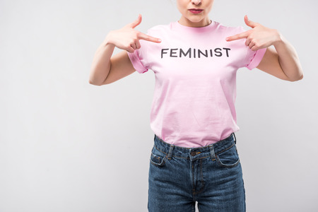 cropped view of woman pointing at pink feminist t-shirt, isolated on grey Banque d'images - 110742276