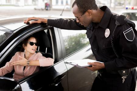 african american policeman with clipboard talking to young woman sitting in car Reklamní fotografie