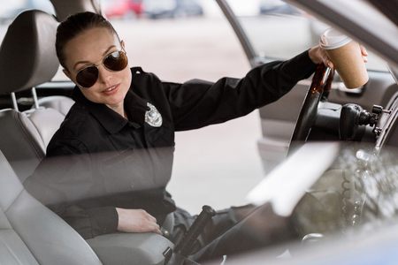 jolie policière avec une tasse de café en papier assise dans la voiture et regardant la caméra