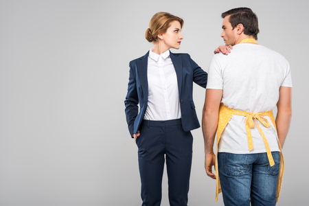 businesswoman and male householder standing together, feminism concept, isolated on grey
