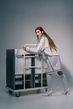 fashionable woman in white clothing and raincoat posing with collapsible chairs behind on grey background Stock fotó - 110753019