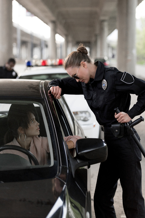 side view of policewoman holding truncheon and talking to young woman sitting in car Stock Photo