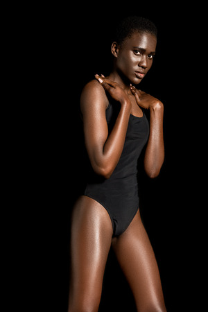 portrait of beautiful african american gil in leotard posing and looking at camera isolated on black