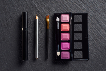 Make up set with eye shadows, pencil and mascara on dark slate background Stock Photo