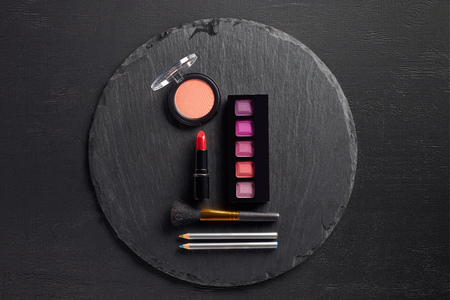 Make up template with eye shadows and lipstick on round slate background