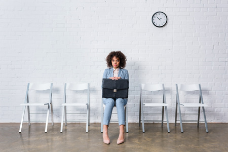 Tense businesswoman with briefcase sitting on chair and waiting