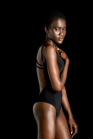beautiful african american woman in swimsuit posing and looking down isolated on black Foto de archivo