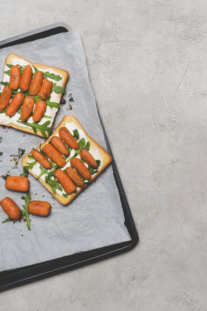 healthy sandwiches with roasted baby carrots and arugula on baking paper on grey Zdjęcie Seryjne