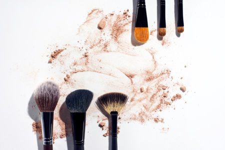 Frame of make up brushes with powder foundation on white background