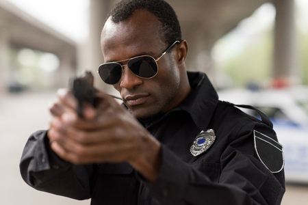 portrait of african american policeman in sunglasses aiming by handgun