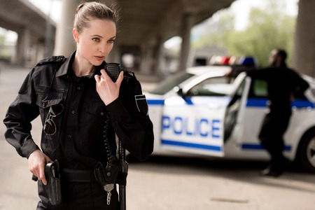 young attractive policewoman using walkie-talkie with blurred partner near car on background