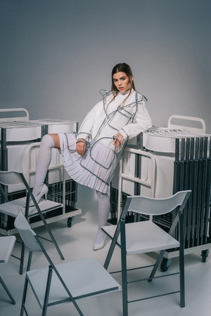 fashionable woman in white clothing and raincoat posing with collapsible chairs behind on grey background Stock fotó