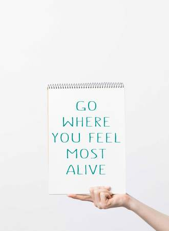 partial view of woman holding sketchbook with Go where you feel most alive inspiration, isolated on white Reklamní fotografie