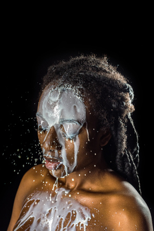 milk spilled on face and naked body of beautiful young african american woman isolated on black