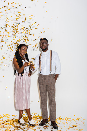 stylish young african american couple smiling at camera while standing on white with golden confetti Stock Photo