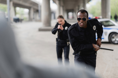 multiethnic police officers running for thief Stock Photo